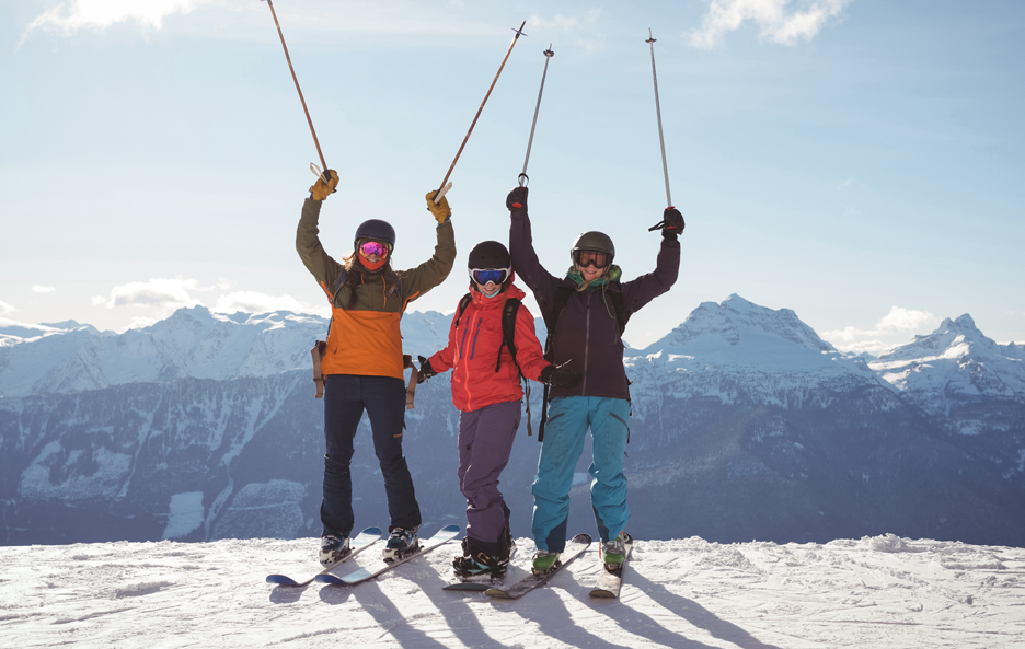 celebrating-skiers-standing-snow-covered-mountain