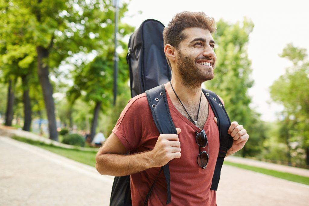 carefree-smiling-guitarist-guy-with-guitar-walking-in-park-happy